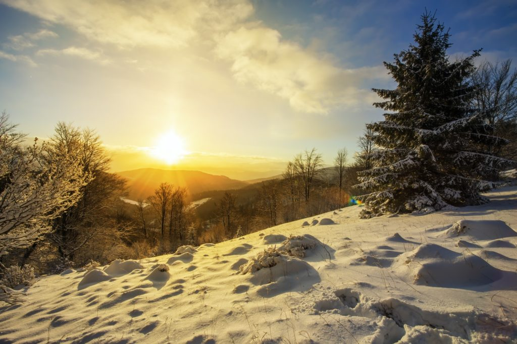 Sun rising above hills covered with snow in winter nature