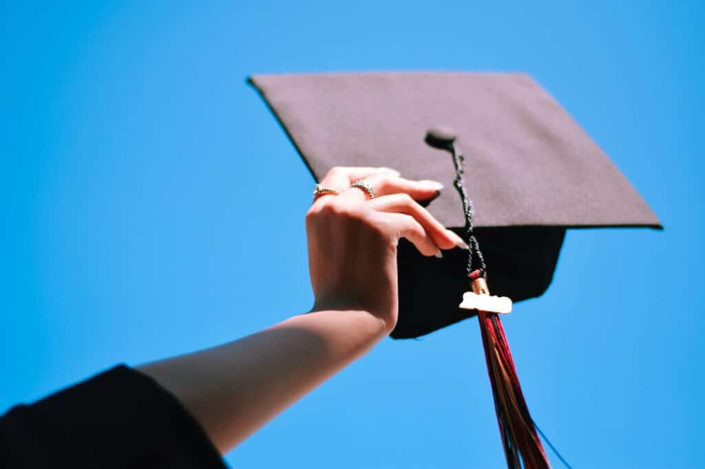 Girl is holding graduation cap up in the air against blue sky
